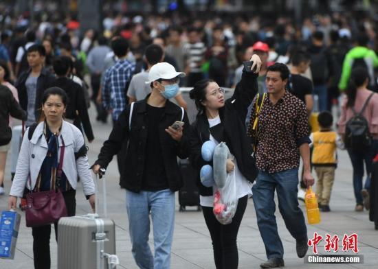 9月30日,全国多地迎来国庆假期客流高峰。图为重庆旅客在火车站广场上玩自拍。 中新社记者 陈超 摄