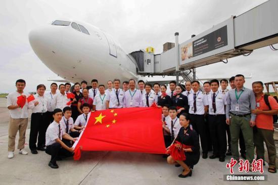 中国驻安提瓜和巴布达使馆和当地中资企业工作人员与东航机组合影留念。殷立勤 摄