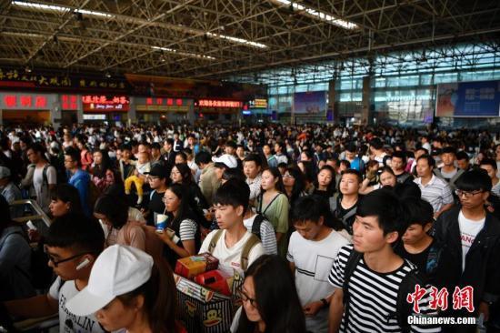 10月1日,旅客排队乘车。当日是国庆长假第一天,昆明火车站迎来出行高峰,客流以旅游、探亲为主。 记者 刘冉阳 摄