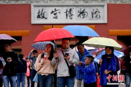 资料图:市民在雨中游览故宫博物院。中新社记者 杜洋 摄