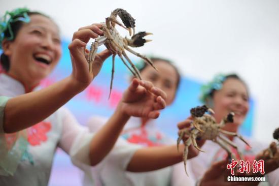 """10月2日,""""渔姑娘""""展示新鲜捕捞的洪泽湖大闸蟹。中新社记者 泱波 摄"""