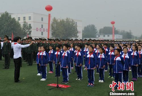 """10月1日9时许,伴随着雄壮的国歌,鲜艳的五星红旗在雄安新区容城县容城中学操场升起。这是雄安新区设立之后,首次举行庆祝国庆""""升国旗、唱国歌""""仪式。图为合唱《歌唱祖国》等曲目。中新社记者 韩冰 摄"""