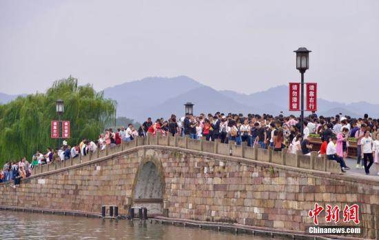 10月3日,国庆长假第三天,大量游客涌入西湖断桥。 记者 李晨韵 摄