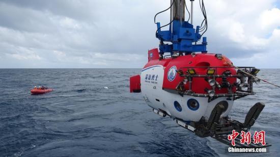 """10月3日,""""深海勇士""""号载人深潜试验队在中国南海完成""""深海勇士""""号载人潜水器的全部海上试验。""""深海勇士""""号载人潜水器是国家""""十二五""""863计划的重大研制任务,由中国船舶重工集团702所牵头、国内94家单位共同参与。图为8月中旬拍摄的载人潜水器(右)和""""蛙人""""。 <a target='_blank' href='http://www.chinanews.com/'>中新社</a>记者 张素 摄"""