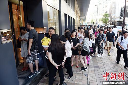 """10月3日,香港迎来内地国庆黄金周的商业机遇。当日,在尖沙咀有""""名店街""""之称的广东道,有不少内地旅客在店外轮候。 <a target='_blank' href='http://www.chinanews.com/'>中新社</a>记者 谭达明 摄"""