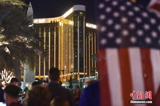当地时间10月3日晚,很多人聚集在美国拉斯维加斯市中心曼德勒海湾酒店附近,悬挂起一面美国国旗,用烛光和鲜花吊唁10月1日晚那场严重枪击事件中的遇难者。 <a target='_blank' href='http://www.chinanews.com/'>中新社</a>记者 张朔 摄