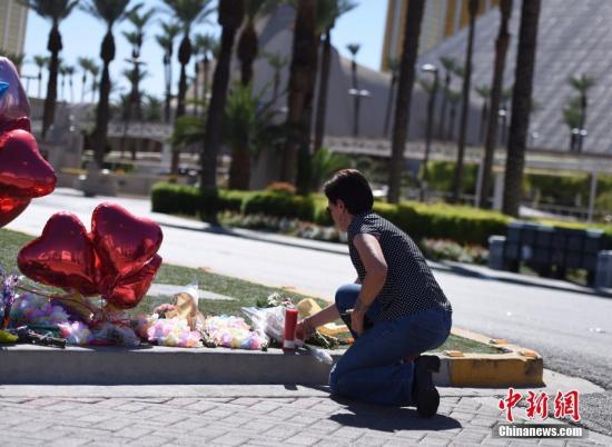 10月3日,位于拉斯维加斯市中心的事发区域依然严密封锁。在现场警戒线内侧,摆放着民众送来的鲜花和气球、蜡烛等。图为一位拉斯维加斯居民前来向遇难者献花致哀。 <a target='_blank' href='http://www.chinanews.com/'>中新社</a>记者 张朔 摄