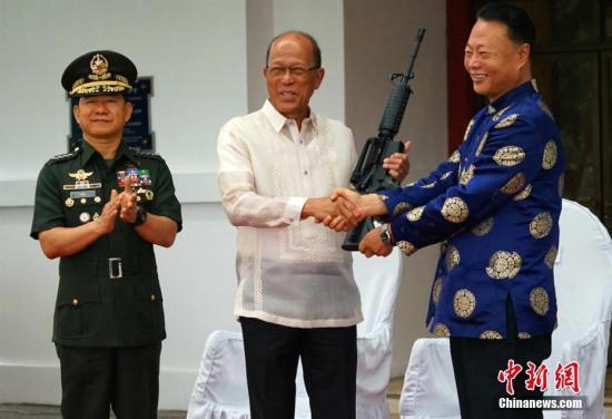 中国驻菲大使赵鉴华10月5日在马尼拉菲武装部队总部,向菲国防部长洛伦扎纳和武装部队总参谋长阿诺移交了中国援助的步枪3000支、子弹300万发,以及狙击瞄准镜90副,价值约3000万元人民币。这是中国今年第二次向菲方提供用以打击恐怖主义的武器装备。图为中国驻菲大使赵鉴华向(右)菲国防部长洛伦扎纳(中)和武装部队总参谋长阿诺移交反恐枪支。 关向东 摄