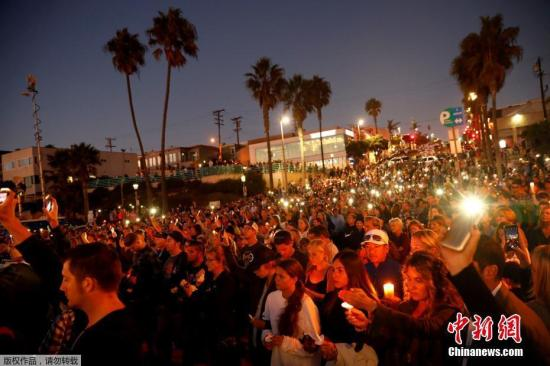 资料图:当地时间2017年10月4日,美国加州曼哈顿海滩,民众和遇难者的亲人朋友集会,手持烛光和灯光,悼念日前拉斯维加斯枪击案遇难者。