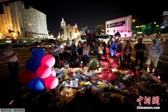 当地时间2018-12-15,美国拉斯维加斯民众在事发现场附近悼念枪击案遇难者。