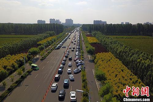 资料图:安新县崇文大街两侧停满前来旅游的车辆。 /p中新社记者 韩冰 摄