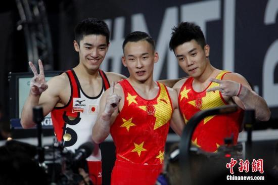 图为肖若腾(中)、林超攀(右)与获得铜牌的日本选手白井健三在比赛结束后合影。 中新社记者 余瑞冬 摄
