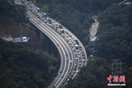 10月6日,京珠高速钟落潭至太和路段大批车辆缓慢行驶。当日,国庆长假接近尾声,广州高速公路开始迎来返程高峰,多条进入广州的高速出现拥堵。 中新社记者 陈骥旻 摄