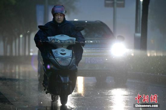北京市民在雨中前行。 中新社记者 刘关关 摄