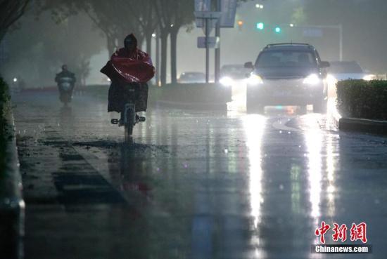 北京市民在雨中前行。 <a target='_blank' href='http://www.chinanews.com/'>中新社</a>记者 刘关关 摄