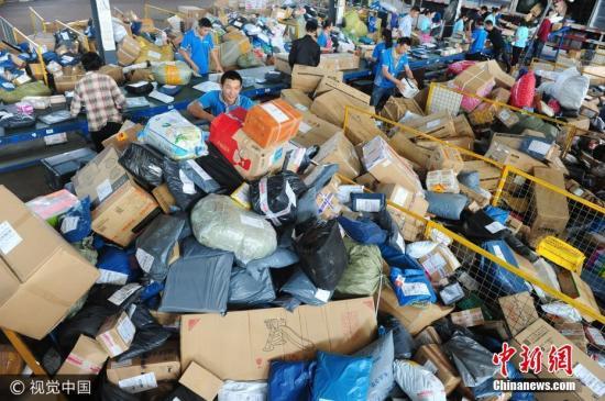 """资料图:10月9日,位于安徽省阜阳市颍东开发区的某快递公司内,快递工作人员在分拣中心忙碌着分拣""""堆如小山""""的快递包裹。王彪 摄 图片来源:视觉中国"""