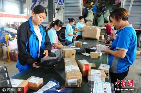 """10月9日,位于安徽省阜阳市颍东开发区的某快递公司内,快递工作人员在分拣中心忙碌着分拣""""堆如小山""""的快递包裹。图片来源:视觉中国"""