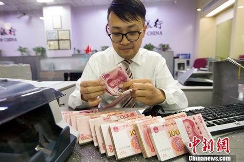 10月9日,来自中国外汇交易中心的数据显示,人民币对美元汇率中间价报6.6493,较前一交易日下跌124个基点,这也是连续6日下调。图为7日,山西太原,银行工作人员清点货币。中新社记者 张云 摄