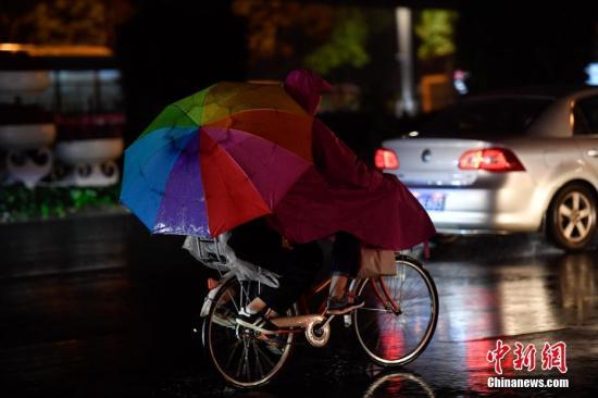 """10月10日,市民雨中骑行。俗话说""""一场秋雨一场寒"""",寒露节气刚过,阴雨天气到访昆明,气温下降,""""春城""""秋意渐浓。中新社记者 刘冉阳 摄"""