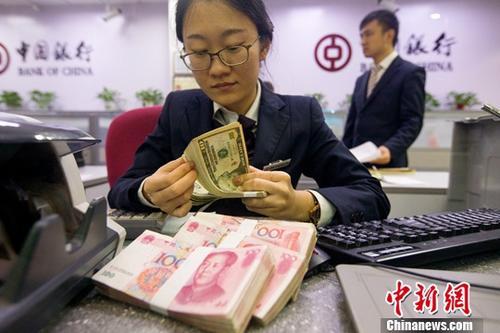 10月10日,山西太原,银行工作人员正在清点货币。当日,来自中国外汇交易中心的数据显示,人民币对美元汇率中间价报6.6273,较前一交易日上涨220个基点。中新社记者 张云 摄