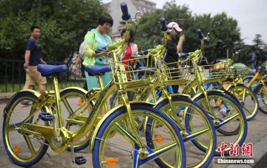 """2017年6月8日,民众在北京街头扫码租用一款""""土豪金""""色的酷骑共享单车。 中新社记者 杨可佳 摄"""