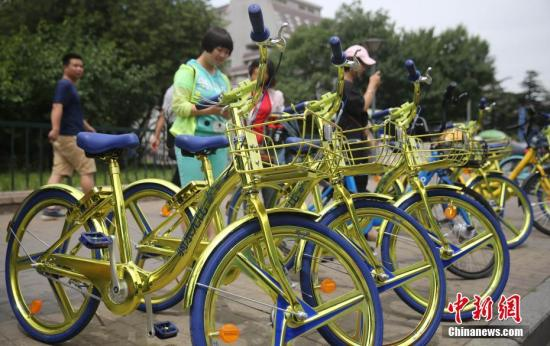 """2017年6月8日,民众在北京街头扫码租用一款""""土豪金""""色的酷骑共享单车。 <a target='_blank' href='http://www.chinanews.com/'>中新社</a>记者 杨可佳 摄"""