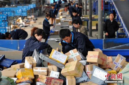 资料图:快递人员正在分拣大量包裹。 中新社记者 韦亮 摄