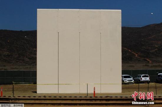 当地时间2017年10月12日,墨西哥提华纳,从美墨边境墨西哥一侧拍摄到的边境墙样品。特朗普2017年1月25日签署行政命令,宣布在美墨边境线上筑墙,以阻挡非法移民和犯罪人员越境从事非法活动。