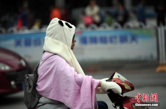 资料图:气温下降,民众穿棉服出行。中新社记者 刘冉阳 摄
