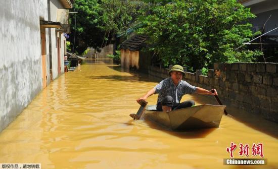 图为当地时间10月12日,越南宁平,当地民众划船出行。由于连日暴雨引发洪涝,街道已成汪洋。