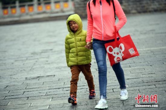 10月13日,受冷空气影响,昆明气温有所下降,民众穿棉服出行。 中新社记者 刘冉阳 摄