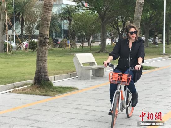 """来华报道十九大的部分外国记者在大会开幕前夕赴广东省走访,寻找中国改革开放、转型创新亮点,他们中不少人对电子商务、移动支付、共享单车等正在中国蓬勃发展的创新经济业态印象深刻。发现街头随处可见""""共享单车"""",外国记者们仔细询问用法,下载软件""""试骑"""",并表示要将这个""""新鲜事""""播报给本国读者。图为来自阿根廷的记者波戈里莱斯在珠海街头试骑共享单车。 肖欣 摄"""