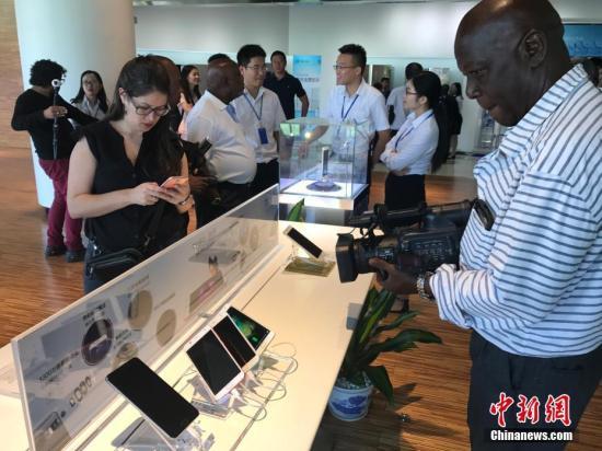 """拉美和加勒比国家记者们在珠海市参观格力集团,体验全球知名的""""中国制造""""产品并向工作人员询问该品牌在拉美等地的销售情况等。肖欣 摄"""