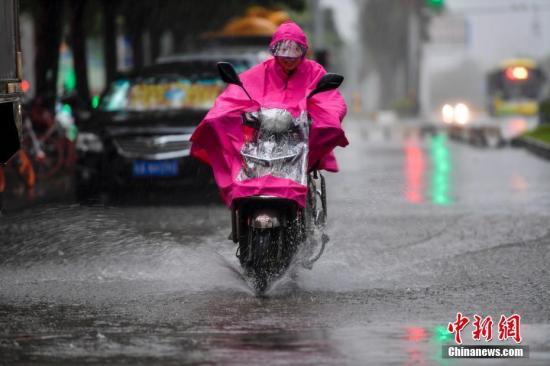 """10月15日,海口民众雨中涉水骑行。今年第20号台风""""卡努""""台风级当日上午开始影响海南,海口市区出现强降水天气。据海口市气象台预计,受""""卡努""""影响,该市15-16日累积雨量150-250毫米,沿岸将出现80-150cm的风暴增水,强降水及风暴增水可能会造成严重内涝。 中新社记者 骆云飞 摄"""