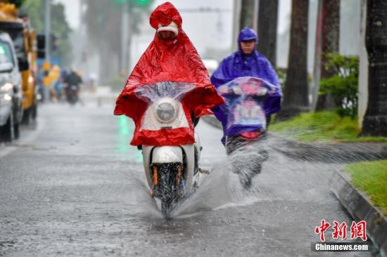 """10月15日,海口民众雨中涉水骑行。今年第20号台风""""卡努""""台风级当日上午开始影响海南,海口市区出现强降水天气。据海口市气象台预计,受""""卡努""""影响,该市15-16日累积雨量150-250毫米,沿岸将出现80-150cm的风暴增水,强降水及风暴增水可能会造成严重内涝。中新社记者 骆云飞 摄"""