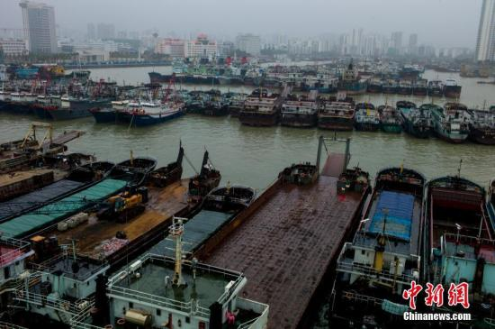 """10月15日,海口新港码头停靠着众多回港避风的船只。15日6时30分,海南省政府继续发布台风二级预警:台风""""卡努""""(台风级),当日6时,中心位于北纬19.9度、东经115.5度,也就是在距离广东徐闻偏东方向约560公里的海面上,中心附近最大风力13级,风速达38米每秒。截至14日23时,海南全省24278艘渔船已全部回港或到安全区域避风,507764名渔船渔排人员全部上岸,转移危房、低洼地带、地质灾害隐患点等危险区域人员共计61412人。 中新社记者 骆云飞 摄"""
