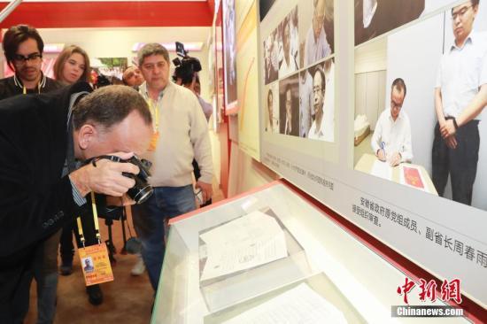 """10月16日,来自拉美、海湾等地区的多个记者团在北京参观""""砥砺奋进的五年""""大型成就展。图为记者们关注十八大以来中共中央党风廉政建设和反腐败工作的进展及成效。 <a target='_blank' href='http://www.chinanews.com/'>中新社</a>记者 盛佳鹏 摄"""