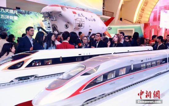 """10月16日,来自拉美、海湾等地区的多个记者团在北京参观""""砥砺奋进的五年""""大型成就展。图为参观的记者们在展厅了解中国复兴号动车组列车。 中新社记者 盛佳鹏 摄"""