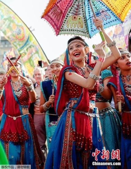 """当地时间10月15日,英国伦敦特拉法加广场上印度舞者们身着传统服饰,跳起加拉巴舞庆祝排灯节。据悉,此次演出由伦敦市长萨迪克・汗发起,借此机会让游客们感受到丰富多彩的异国文化。排灯节,又称万灯节、印度灯节或者屠妖节。是印度教、锡克教和耆那教""""以光明驱走黑暗,以善良战胜邪恶""""的节日。于每年10月或11月中举行,一些佛教信徒也庆祝这个节日。"""