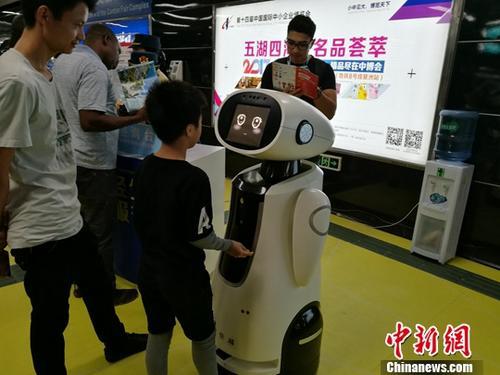 """第122届广交会1O月15日开幕,广州地铁推出机器人""""智能AI服务"""",机器人""""小悠""""在琶洲地铁站为乘客提供智能咨询及引导服务。中新社记者 王华 摄"""