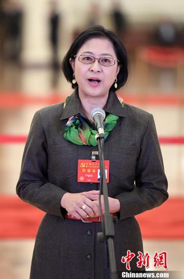 """10月18日,中国共产党第十九次全国代表大会在北京人民大会堂开幕。开幕前举行首次""""党代表通道""""采访活动。图为卢丽安代表接受采访。 中新社记者 毛建军 摄"""