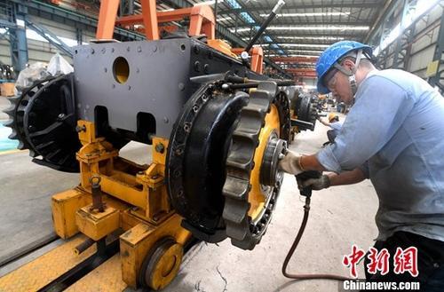 图为厦工(三明)重型机器有限公司工人在生产线上作业。(资料图片)中新社记者 张斌 摄