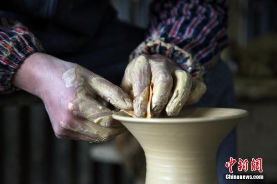 """在贵州省遵义市播州区花茂村有一种已经传承百年的土陶制作技艺。土陶技艺的第四代传承人母先才说:""""传承土陶是我的责任,无论如何我都不会让先辈创造的技艺流失""""。如今,土陶已被列为市级非物质文化遗产,传统的爬坡窑也被环保的陶器烧制机取代。图为母先才细心制作土陶器具。 <a target='_blank' href='http://www.chinanews.com/'>中新社</a>记者 瞿宏伦 摄"""