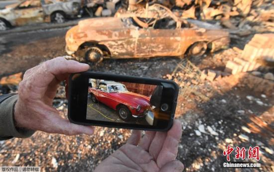 当地时间10月20日,美国加州圣罗莎山火过后,民众返回被烧毁的房屋凭吊曾经家园,并在废墟中寻找私人物品。图为汽车收藏者Gary Dower在展示被烧毁前的1973年款MGB Roadster。