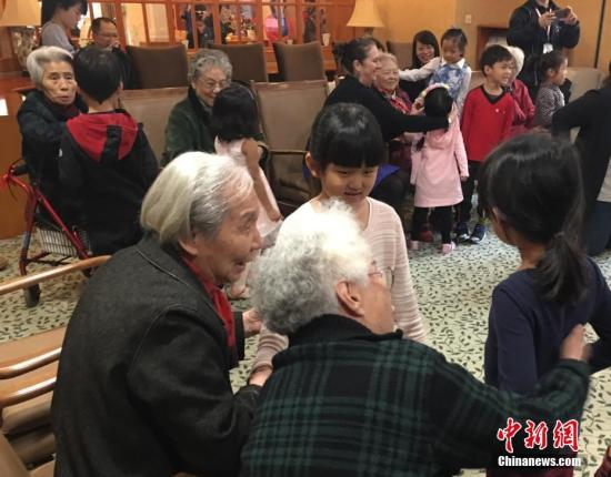 图为在养老院,老人们与幼儿园小朋友一起做游戏。中新社记者 杜燕 摄