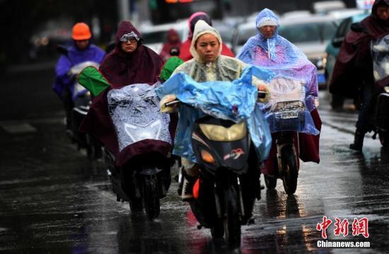 10月23日,昆明市区里冒雨赶路的民众。霜降节气,昆明迎来降雨又降温的天气,气温降到8℃。霜降是24个节气里,秋季的最后一个节气,从此天气开始渐冷。 记者 李进红 摄