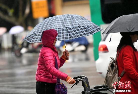 10月23日,昆明市区里身着羽绒服冒雨赶路的民众。霜降节气,昆明迎来降雨又降温的天气,气温降到8℃。霜降是24个节气里,秋季的最后一个节气,从此天气开始渐冷。 中新社记者 李进红 摄