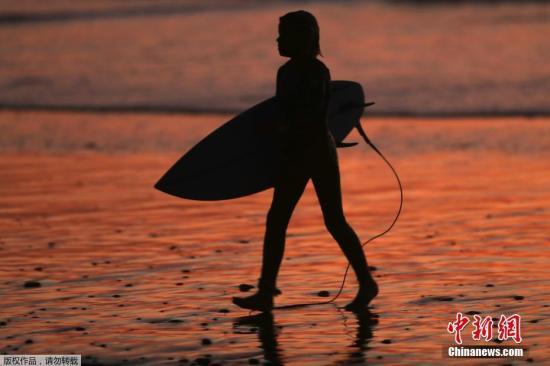 资料图:落日下的沙滩,游客在悠闲享受生活。