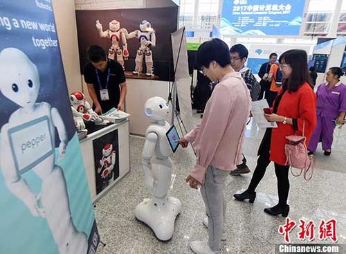 """10月26日,以""""人工智能改变世界(AIChangestheWorld)""""为主题的2017中国计算机大会(CNCC2017)在福州海峡国际会展中心开幕。图为大会展览展示区内,一港资参展企业展示的智能机器人吸引参会人士的眼球。 <a target='_blank' href='http://www.chinanews.com/'>中新社</a>记者 刘可耕 摄"""