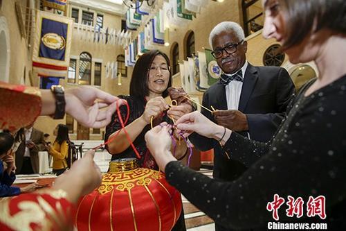 """当地时间10月25日,中国驻纽约总领馆在马萨诸塞州议会大厦举办""""新时代、新起点――互利共赢的中美合作""""主题中国日活动。图为来宾在中国结展台体验系中国结。 中新社记者 廖攀 摄"""